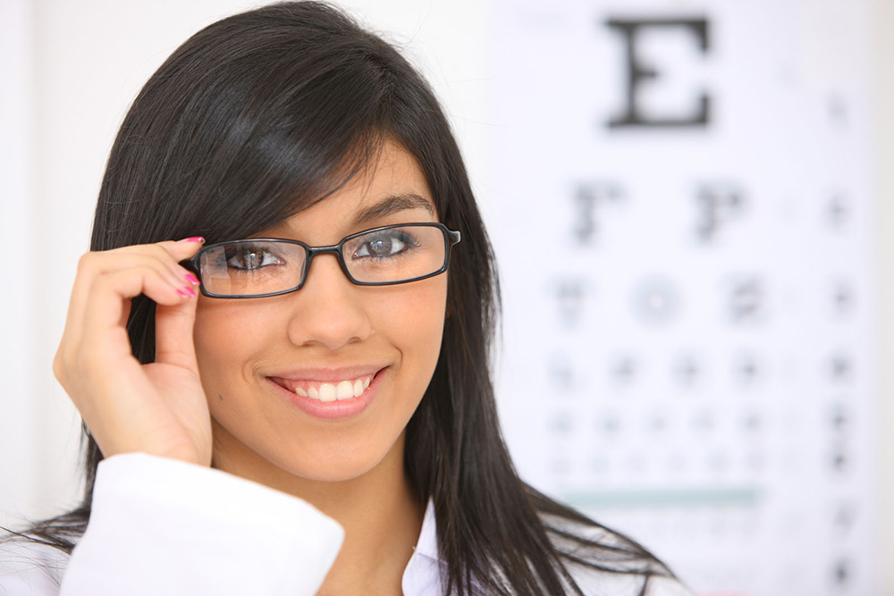 woman wearing glasses with blurry eye chart behind her